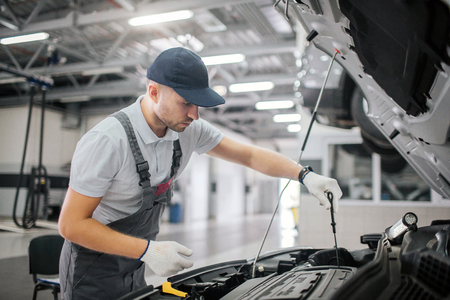 Man stands at opened body of car and works. He is serious and concentrated. He holds black wrench in right hand. Guy works in gloves.
