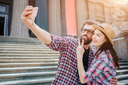 Young man and woman stand together and takes selfie. He holds camera in hand. They pose. People stand on stairs.