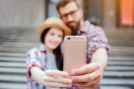 Picture of couple holding phone together and look at him. They smile. Tourists stand in front of stairs. They pose.