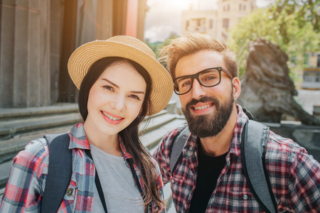Nice picture of two young tourists looking on camera and smiling. Man and woman stand outside close to stairs. They have rocksacks on back. People are positive and beautiful. 写真素材