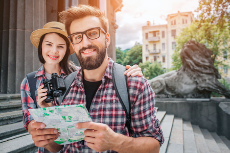 Two tourists stand close to steps outside. They look on camera and smile. Bearded man holds map in hand. They are cheerful. Woman holds binoculars.
