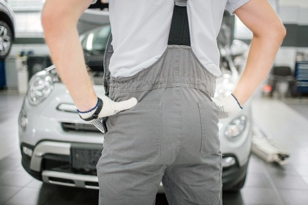 Picture of male body stands in front of car. Man holds his hands on hips. He wears gloves. It is his buttocks shown to camera.