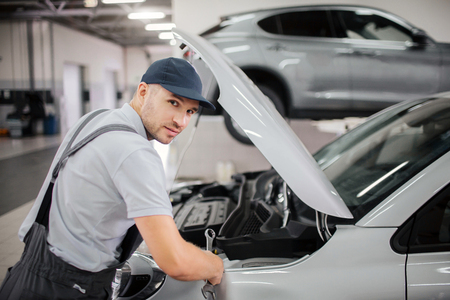 Handsome young worker looks on camera. He makes repairs in front body of car. Guy wears cap and uniform.