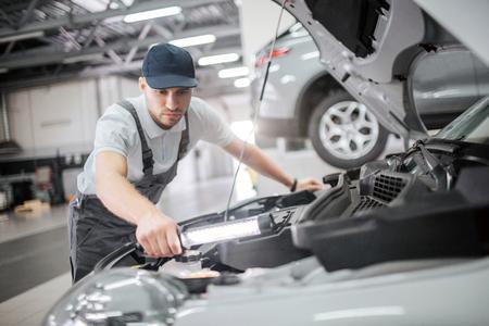 Poważny i skoncentrowany człowiek stoi przy otwartej karoserii samochodu i detalach naprawy. Jest spokojny i skoncentrowany. Facet trzyma w ręku klucz. On go używa. Zdjęcie Seryjne