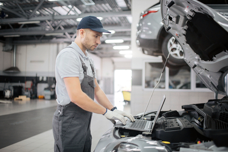Picture of young worker type on keyboard. He looks at screen of laptop. Guy is doing diagnostics for car. He checkes its condition.