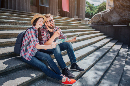 Tourists sit on steps and look forward. Young man points. They smile. People hold map together. It is sunny outside.