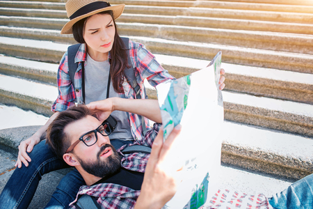 Picture of serious tourists on steps. He is lying on girlfriends knees and hold map in hanad. She sits on steps. They are confused and concentrated.