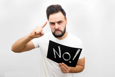 Serious and angry man stand and hold plate with written word no. He points up and look scarely on camera. Allso man looks like threat. Isolated on white background.