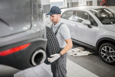 Young man stands in front of trunk and hold tire with both hands. He looks at it with seriousness. White car is behind him.