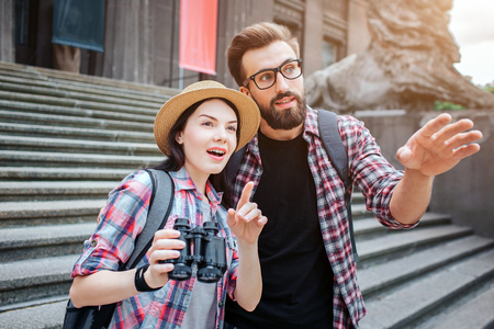 Amazed tourists stand in front of stairs. They point forward. Woman holds binoculars. They are in city. Bearded guy wears glasses. 写真素材