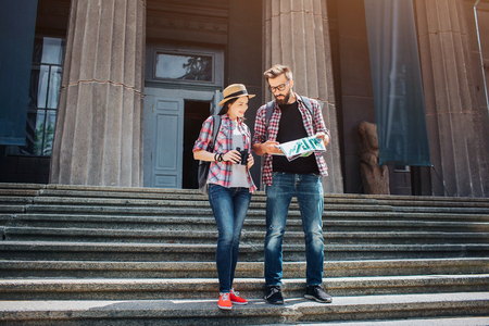 Young tourists stand on stairs and lok on map. They study it Guy is concentrated. Young woman smiles. She holds binoculars.