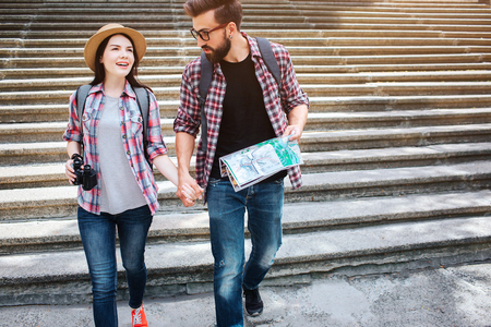 Beautiful couple walk together. They hold each others hand. Young man look at woman. He holds map. They walk on stairs. 写真素材