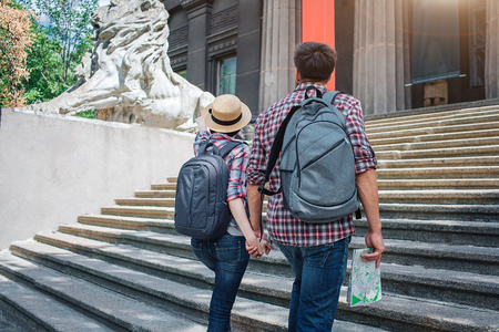 Two tourists walk up on steps and hold each others hand. They look forward. He has map in hand. Both have rocksacks on back.