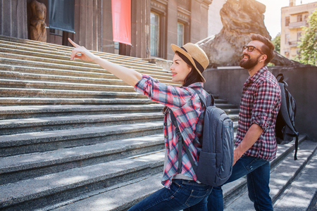 Male and female tourists walk up on steps. She points forward. They hold each others hands and have rocksacks on back. People look nice and positive.