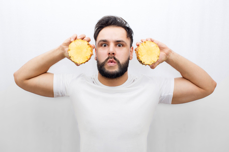 Really amazed young man stand and look on camera. He coveres ears with two halfs of one pineapple. Guy is scared and amased. Man in distracted. Isolated on white background. Foto de archivo - 111168500