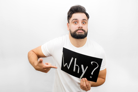 Strange young man showing emotion on face and looking at camera. He holds polate with written word Why. Also he points on it. Isolated on white background.