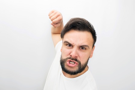 Very angry man looks on camera. He is ready to fight with fist. He poses. Isolated on white background.