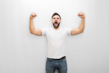 Young man screaming and yelling while posing. He is strong. Guy shows his muscles. Isolated on white background. Banque d'images - 110905487