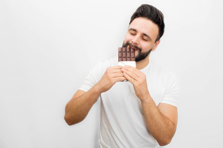 Picture of young bearded man eating delicious chocolate. He bites it with eyes closed. Isolated on white background.