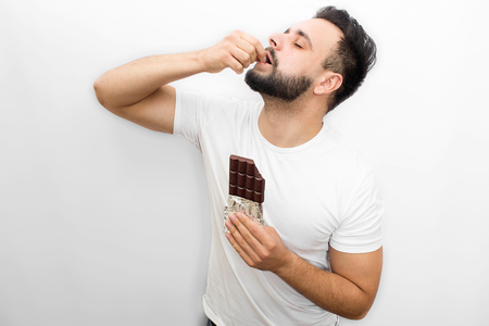 Picture full of pleasure. Young bearded man stands and eats chocolate. He puts piece of it into mouth. Guy keeps eyes closed. Man is concentrated. Isolated on white background. Imagens