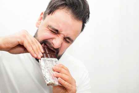 Bearded fat man biting chocolate. it is hard for him to do that. Young man holds bar with both hands. Isolated on white background.