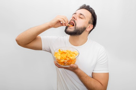 Man in white shirt stands and eats chips. He puts it in mouth with hand. Also guy has a bowl with them in another hand. Its delicious. Isolated on white background.