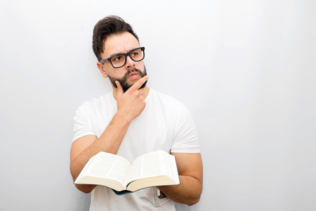 Wize and thoughtful young man in glasses stand and hold opened book in hands. He looks to side. Guy holds hand on chin. Isolated on white background.