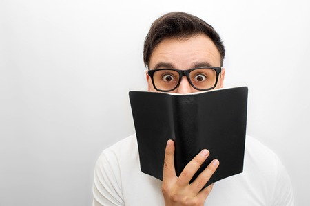 Picture of male brunette looking on camera. He holds black book in hands. He weas glasses. Young man is excited. Isolated on white backgorund.