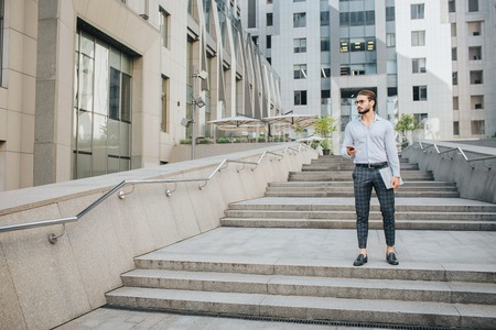 Serious and handsome young man stand and pose. He looks to right. Businessman holds phone and laptop in hands. He is surrounded with buildings. Stock Photo