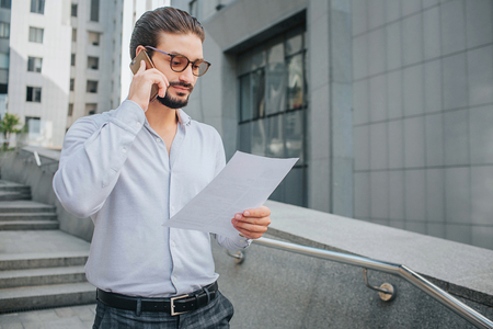 Bearded businessman in sunglasses stands on steps and hold piece of paper. He looks at document. Guy studies it. e talkes on phone at the same time.