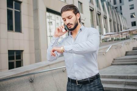 Young businessman is very busy. He looks at watches on his hand. Also bearded guy talks on phone. He runs on steps.