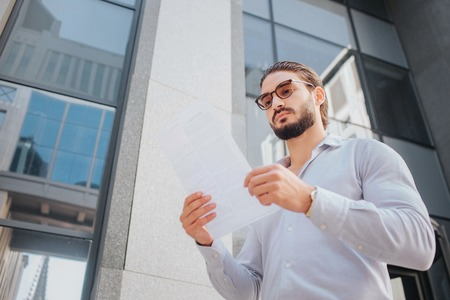 Picture of young stylish man stand and poses. He looks at white piece of paper through sunglasses. Guy is calm, peaceful and concentrated. He stands in front af glass building. Banco de Imagens