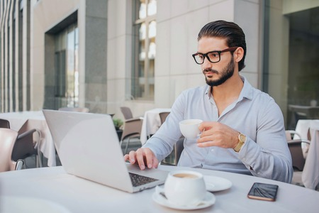 Businessman in glasses sits at white table and works on laptop. He holds cup of coffee in hand. Guy is serious and concentrated. Phone is at table.