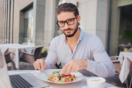 Young handsome man sits at table and has lunch. He looks at camera. Guy poses. He is ready to eat salad. There are laptop and cup of coffee at table.