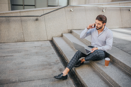 Picture of young businessman sits on steps and works. He talks on phone and looks at laptops screen. Young man keeps his legs crossed.