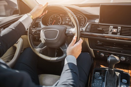Cut view of mans hands in suit. Guy sits in car and holds hands on steering wheel. He drives.
