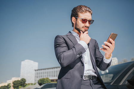 Busy young man looks at phone he holds in hands. Guy has another hand on chin. He thinks. Young man stands at black car.