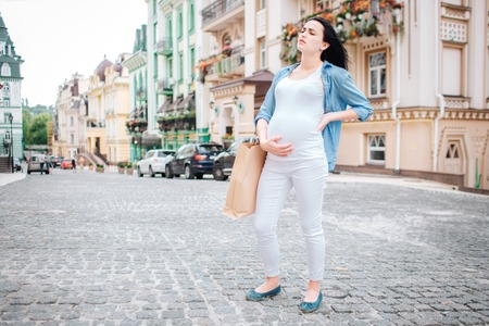 pregnancy, motherhood, people and expectation concept - close up of pregnant woman with shopping bags at city street. Feeling unwell, she has stomach and back pain. Фото со стока