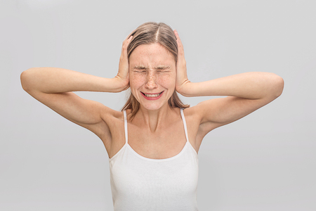 Young woman suffers from headache. She coveres ears with hands and keeps eyes closed. Young woman wears white t-shirt. Isolated on grey background.