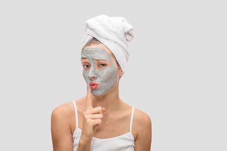 Young woman keeps finger on her lips. She has mud mask on her face. Also there are white t-shirt on her body and towel around hair. Isolated on grey background. Foto de archivo