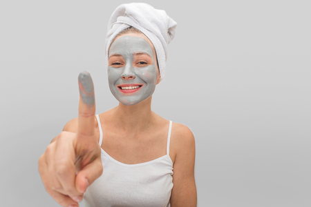Happy young woman points on camera with finger of mud mask. She smiles. Young woman wears white t-shirt on body and towel around hair. Isolated on grey background. Stock Photo