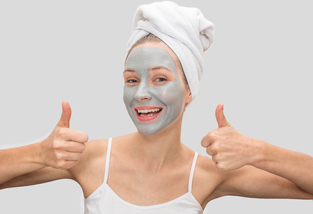 Positive and funny young woman shows her big thumbs up. Model smiles. She has mud mask on her face. Woman has white towel around her hair and t-shirt on body. Isolated on grey background.