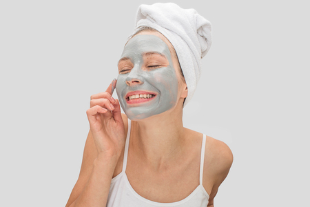 Happy and lovely young woman keeps eyes closed and touches her face with finger. She has mask on skin of her face. Model smiles. She looks happy. Isolated on grey background. Stock Photo
