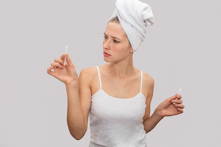 Young woman stands and holds ear sticks in hands. She looks at them and wonderes. Model wer white t-shirt and white towel around her hair. Isolated on grey background.