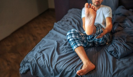 Young man sits on bed and shows his foot on camera. He holds leg with both hands. Guy is in bedroom. Cut view. Stockfoto