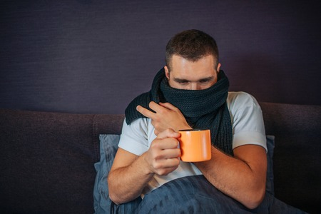 Picture of young sick man sitting on bed and holding orange cup of tea. He looks at it. Guy coveres his mouth with scarf. He got cold. Stock Photo