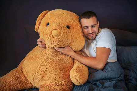 Nice picture of adult with big orange bear toy. Guy embrace and leans to it. He keeps eyes closed. Man has rest. He is sick. 版權商用圖片