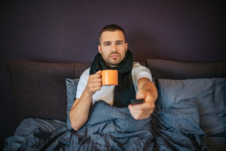 Sick young man sits on bed in bedroom and uses remote control. He looks straight forward. Guy has orange cup in hands. He is calm and concentrated. There are scarf arounf his neck. 版權商用圖片