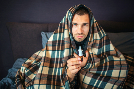 Sick young man looks on camera. He holds nose spray in hand. Guy is serious, He is completely covered with blanket. Young man is in bedroom. Stock fotó