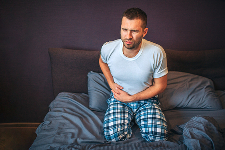 Young man stands on knees on bed and suffers from pain in appendix area. He holds hands there. Guy shrinks. He wear pajamas. Stock fotó